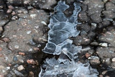 Asphalt cracks full of ice
