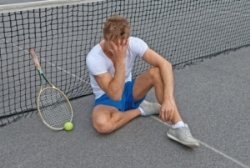 A frustrated tennis player with their hand to their forehead sitting against the net